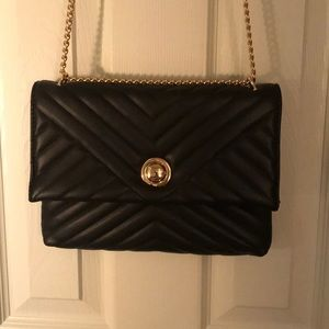 Black purse with gold accent and chain